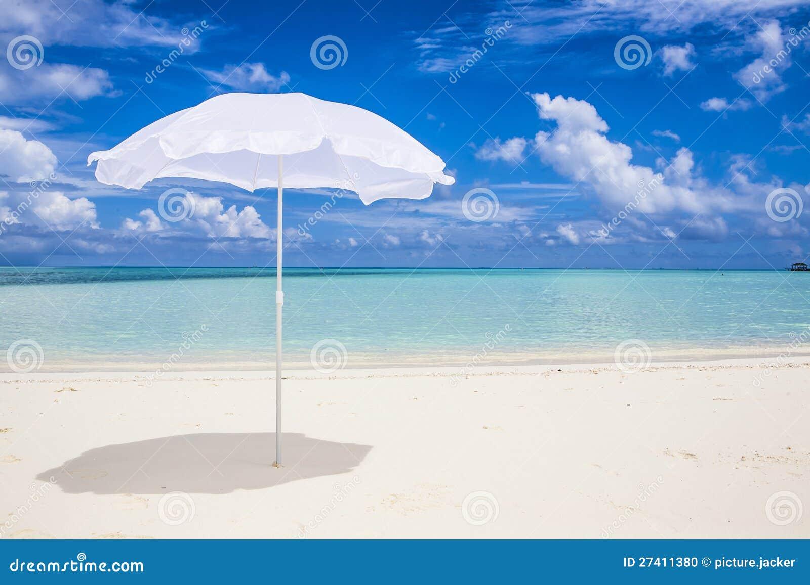 Vit parasoll på stranden