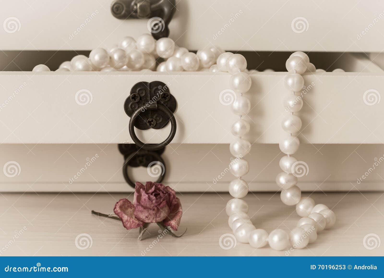 Vit pryder med pärlor halsbandet i en träcasket