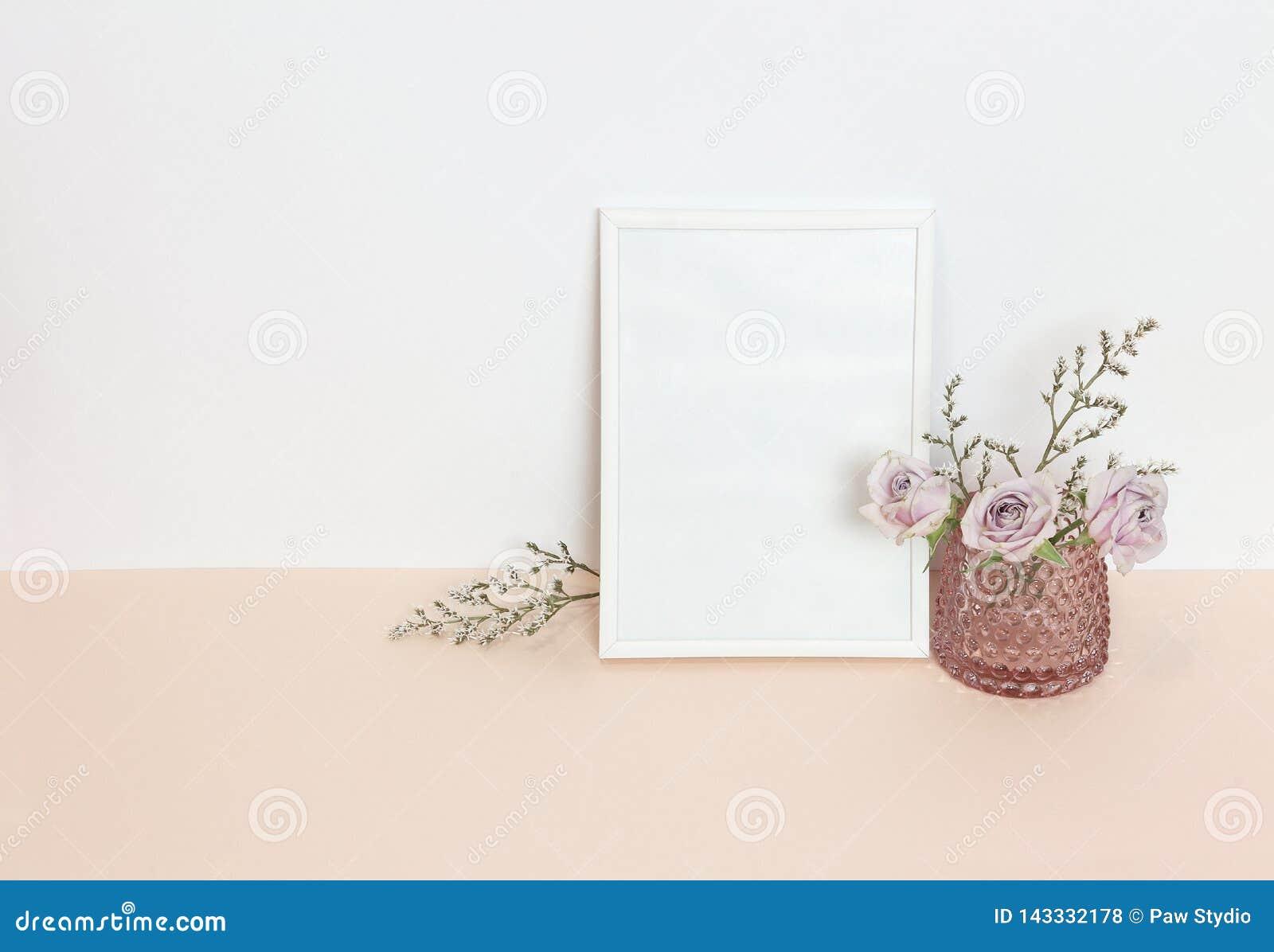 Vit ram med blommor på skrivbordet