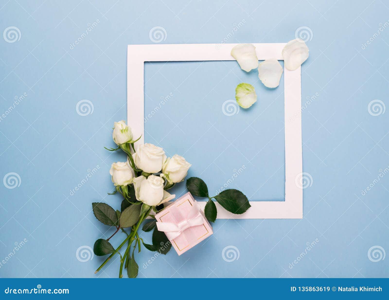 Vit vit ramgåva för rosor och dekorerade med nya sidor på en blå bakgrund Plan orientering kopiera avstånd