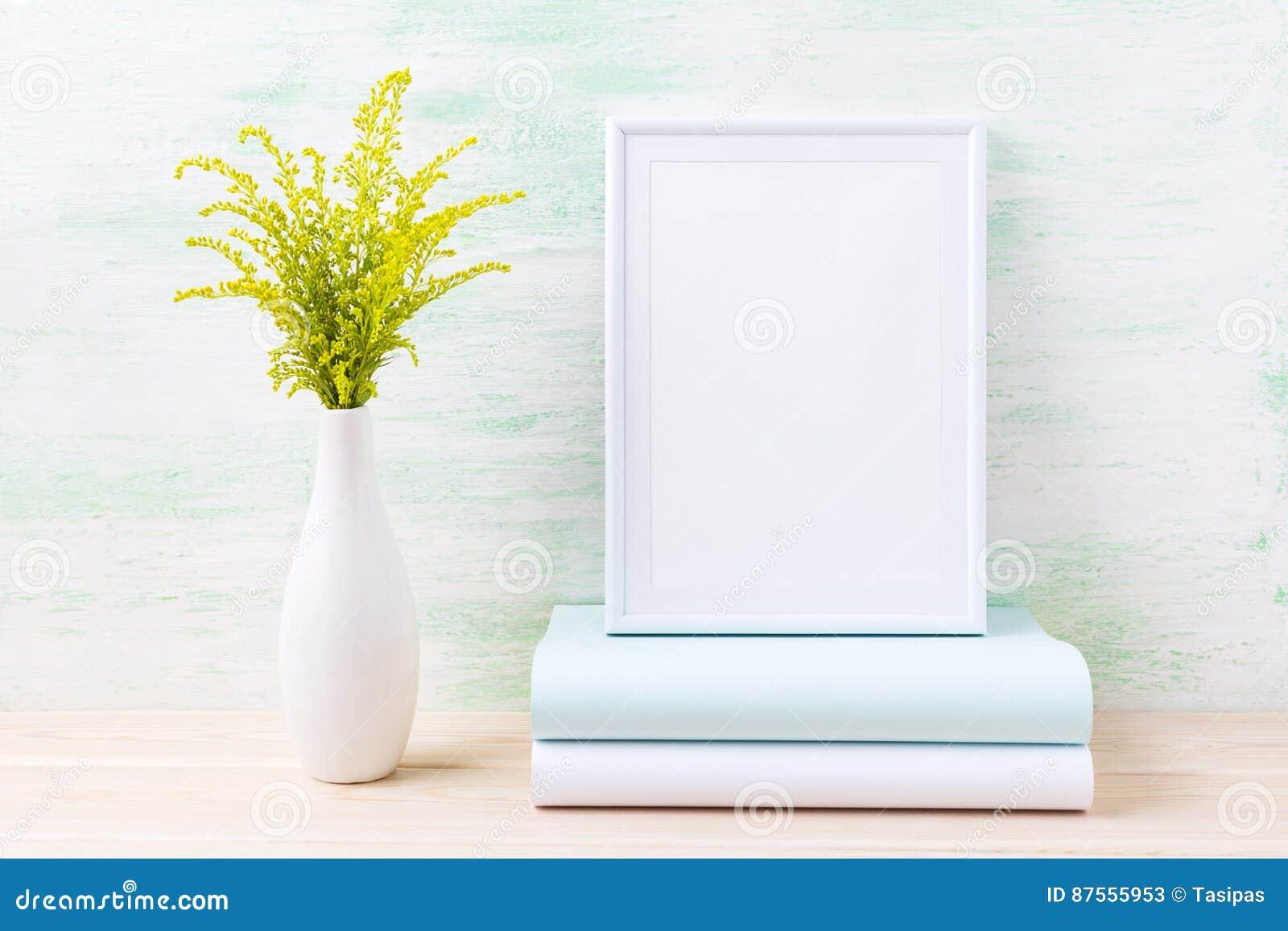 Vit rammodell med dekorativt grönt gräs och böcker