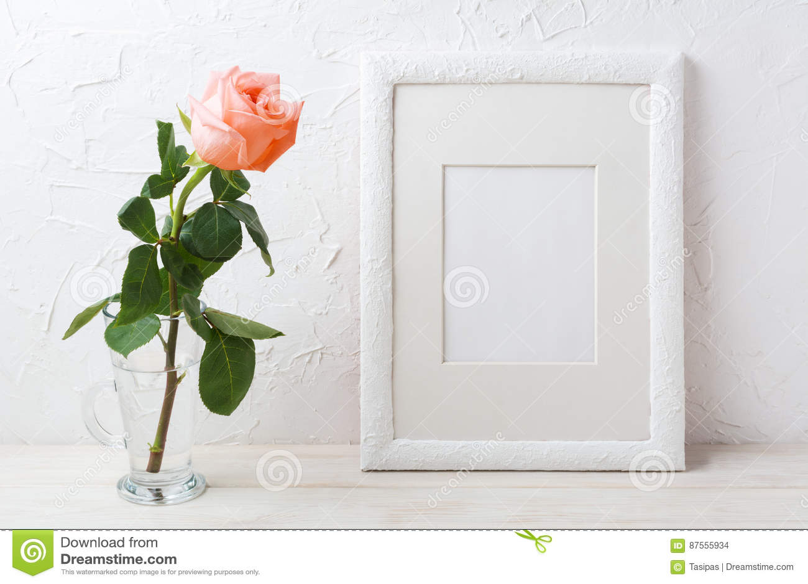 Vit rammodell med den krämiga rosa färgrosen i den glass vasen