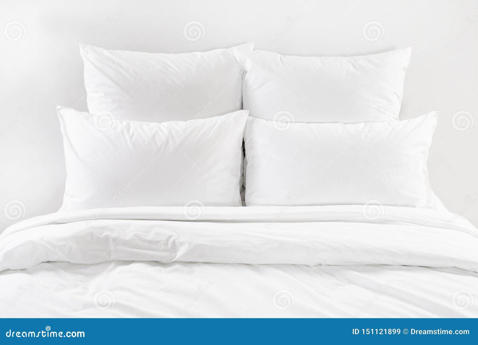 Vit säng, fyra vita kuddar och duntäcke på en säng