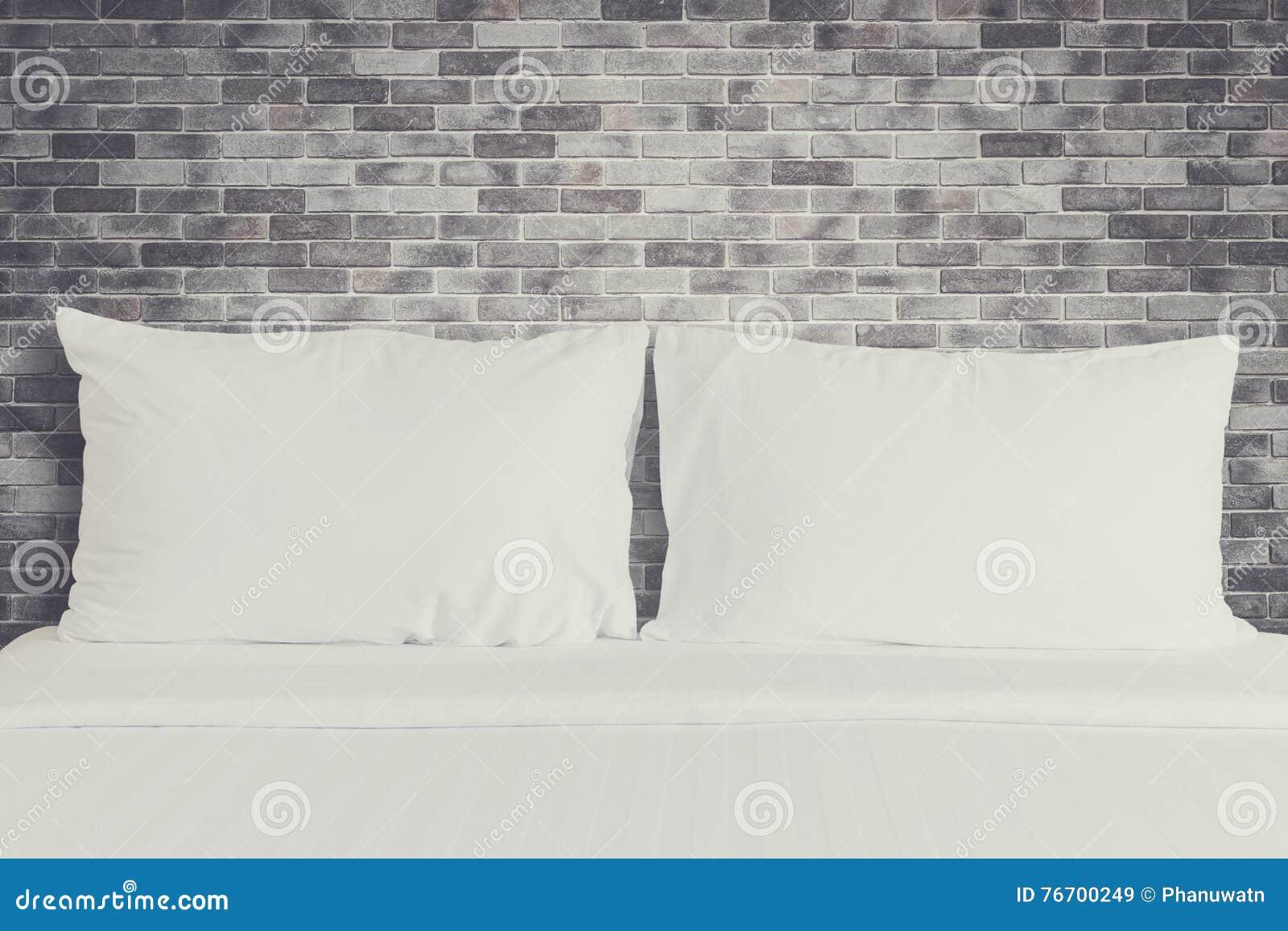 Vit sängkläderark och kudde i hotellrum