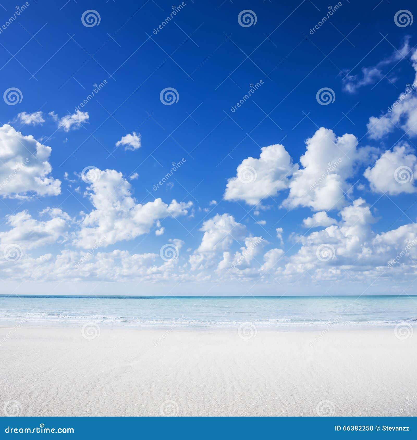 Vit sandstrand, tropiskt hav och blå himmel