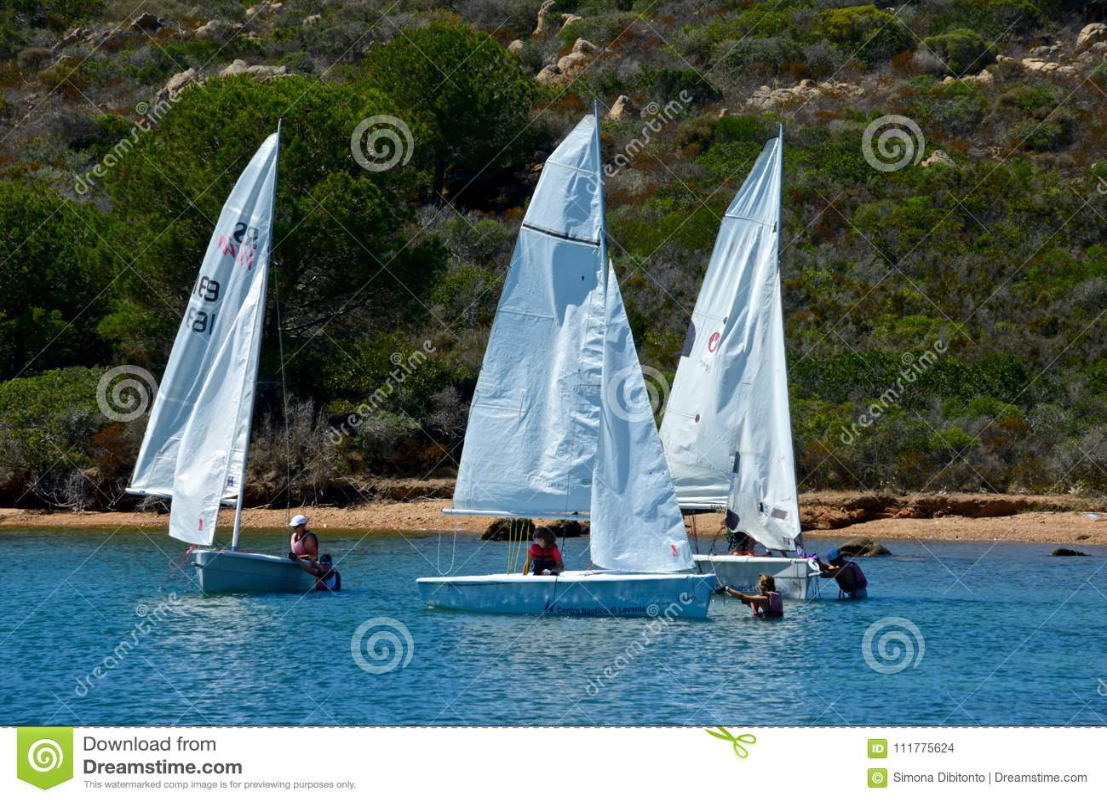 Vit seglar fartyg med folk som lär att segla i det blåa havet som av naturen omges