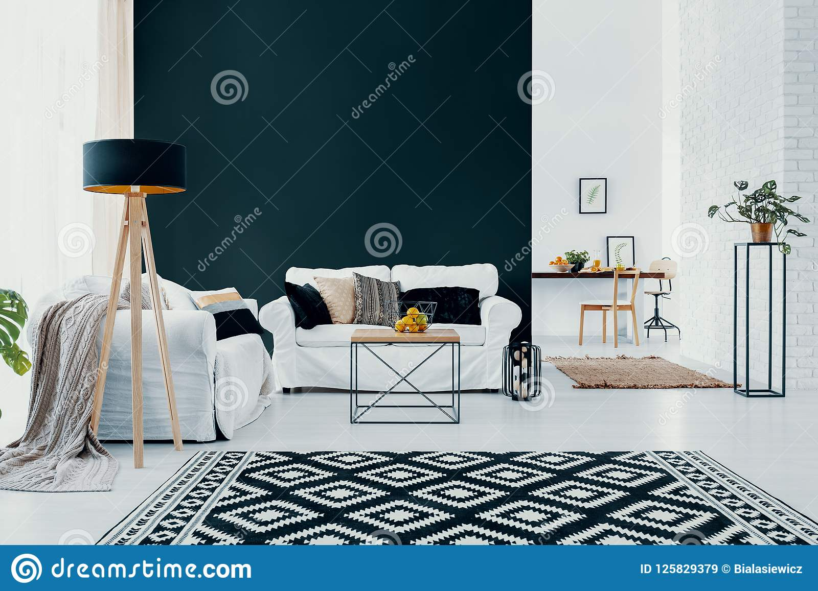 Vit soffa mot den svarta väggen i modern vardagsruminre med mönstrad matta Verkligt foto