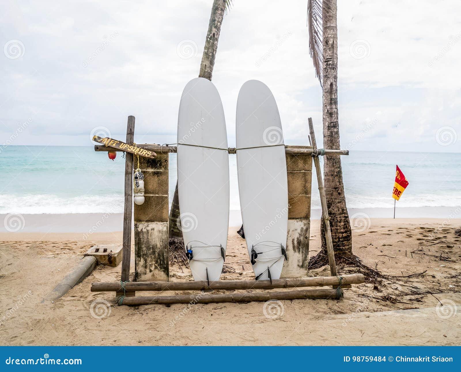 Vit surfingbräda som överges på en tom sandig strand med vågor i avstånd