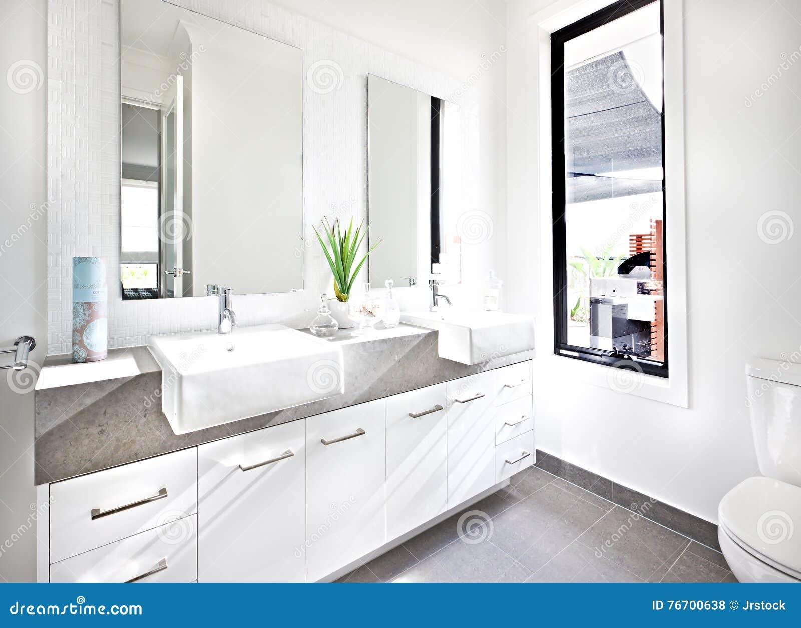 Vit toalett som är upplyst med solljus runt om räknaren