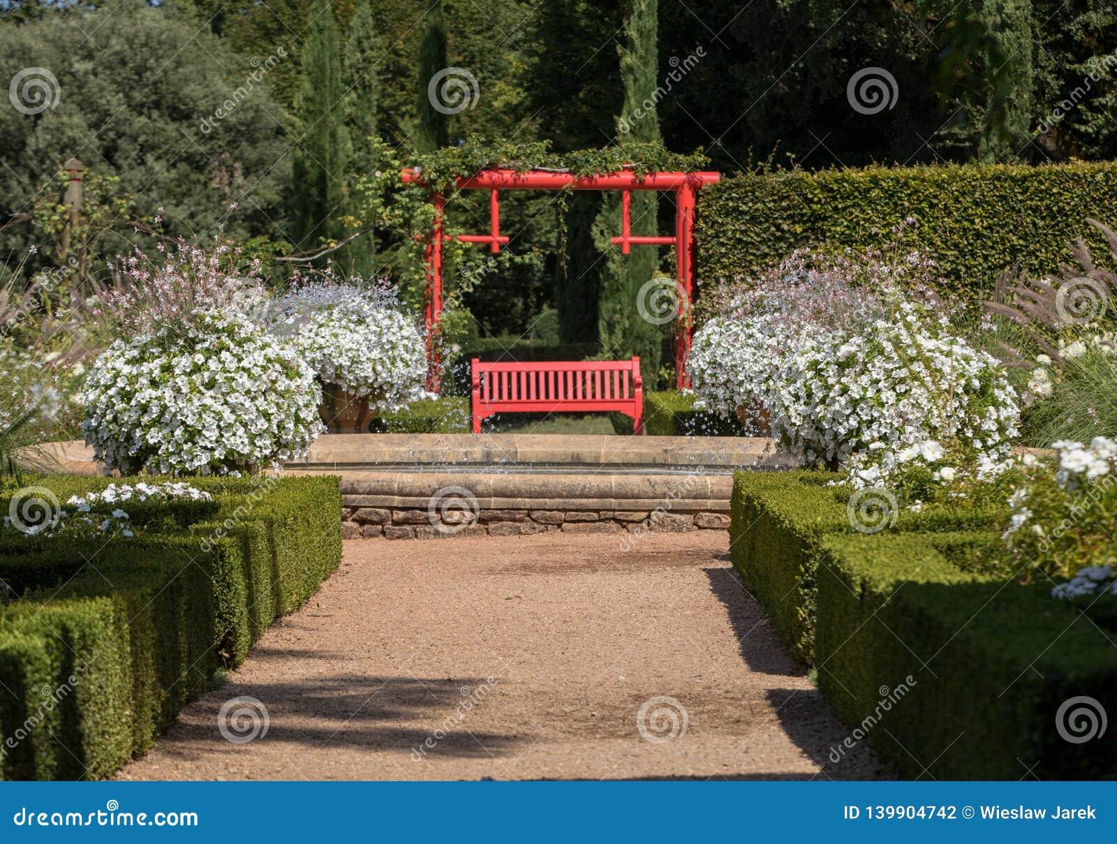 Vit trädgård i den pittoreska Jardinsen du Manoir D Eyrignac i Dordogne