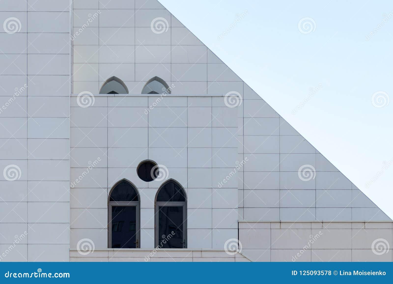 Vit vägg med välvda och runda fönster, detalj av byggnadsyttersida, stads- geometri