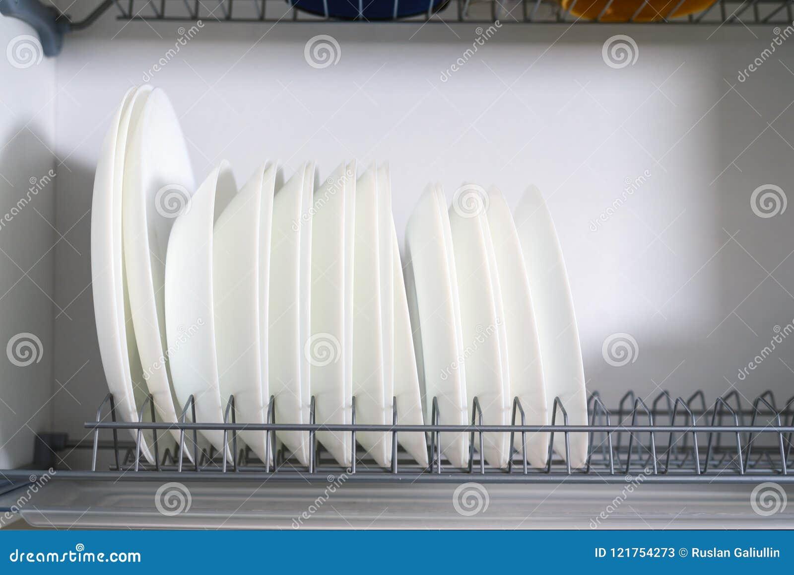 Vita keramiska plattor som i rad staplas i en uttorkningskåpnärbild