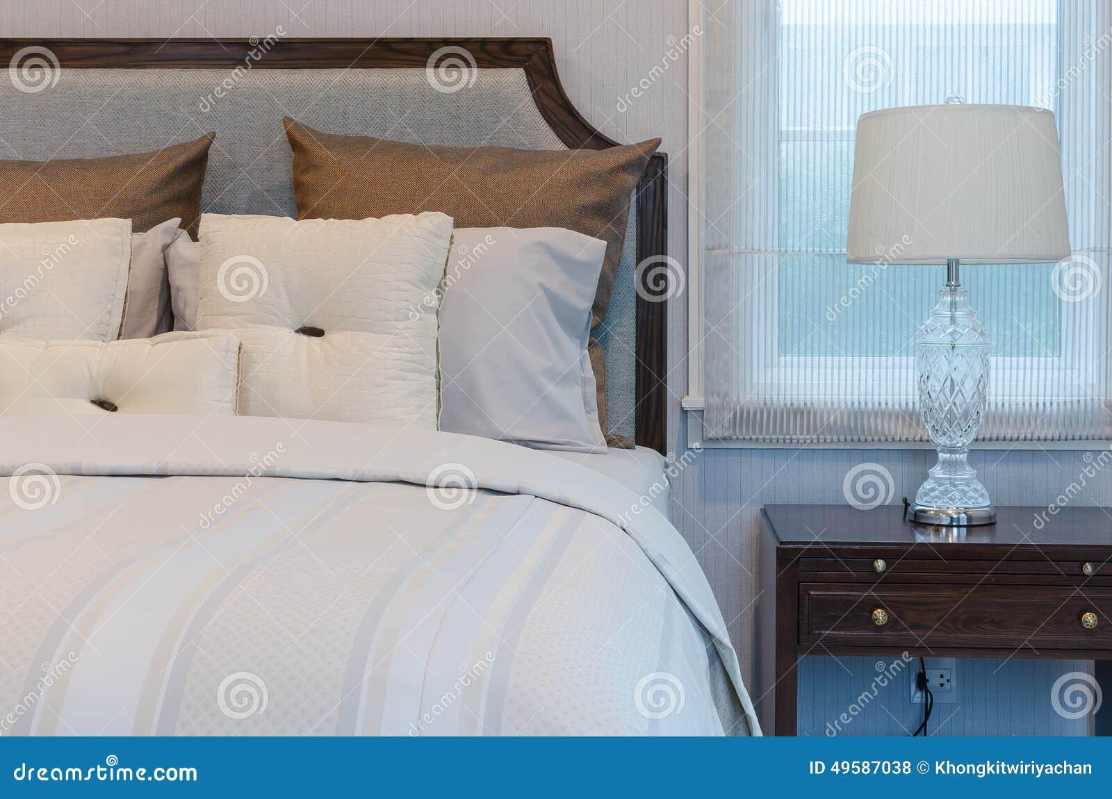 Vita kuddar på vit säng med den lyxiga lampan i sovrum arkivfoto ...