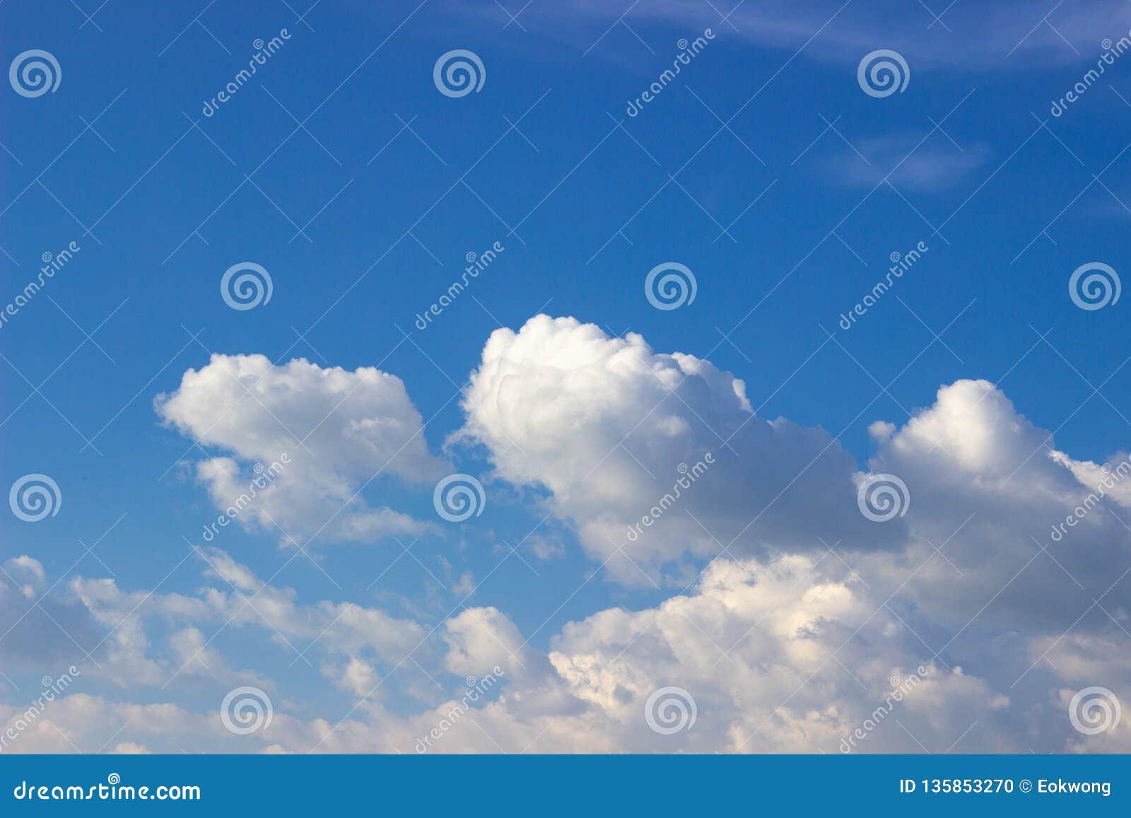 Vita moln på en solig dag, mot den blåa himlen