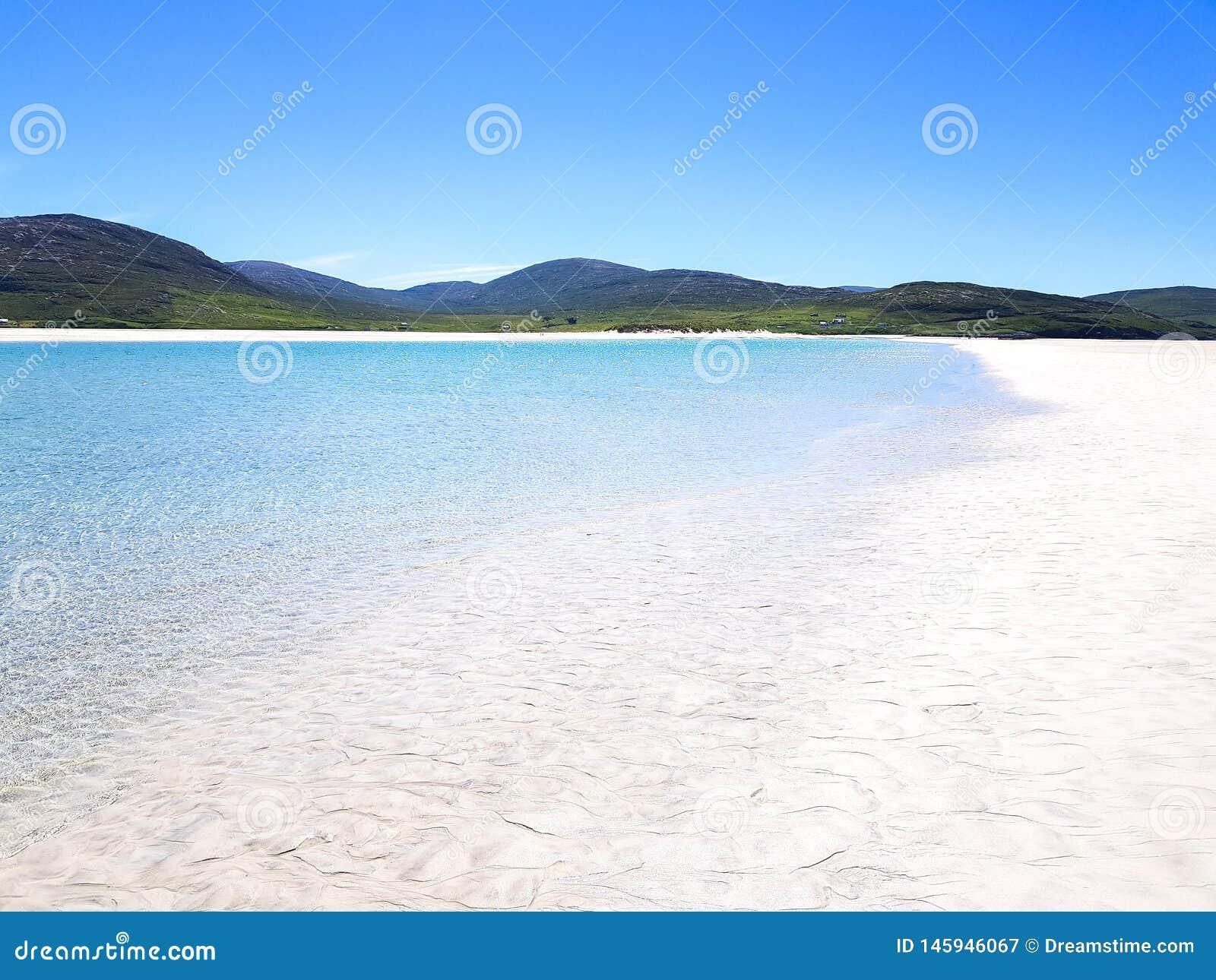 Vita sander och bl?tt vatten p? en skotsk ?
