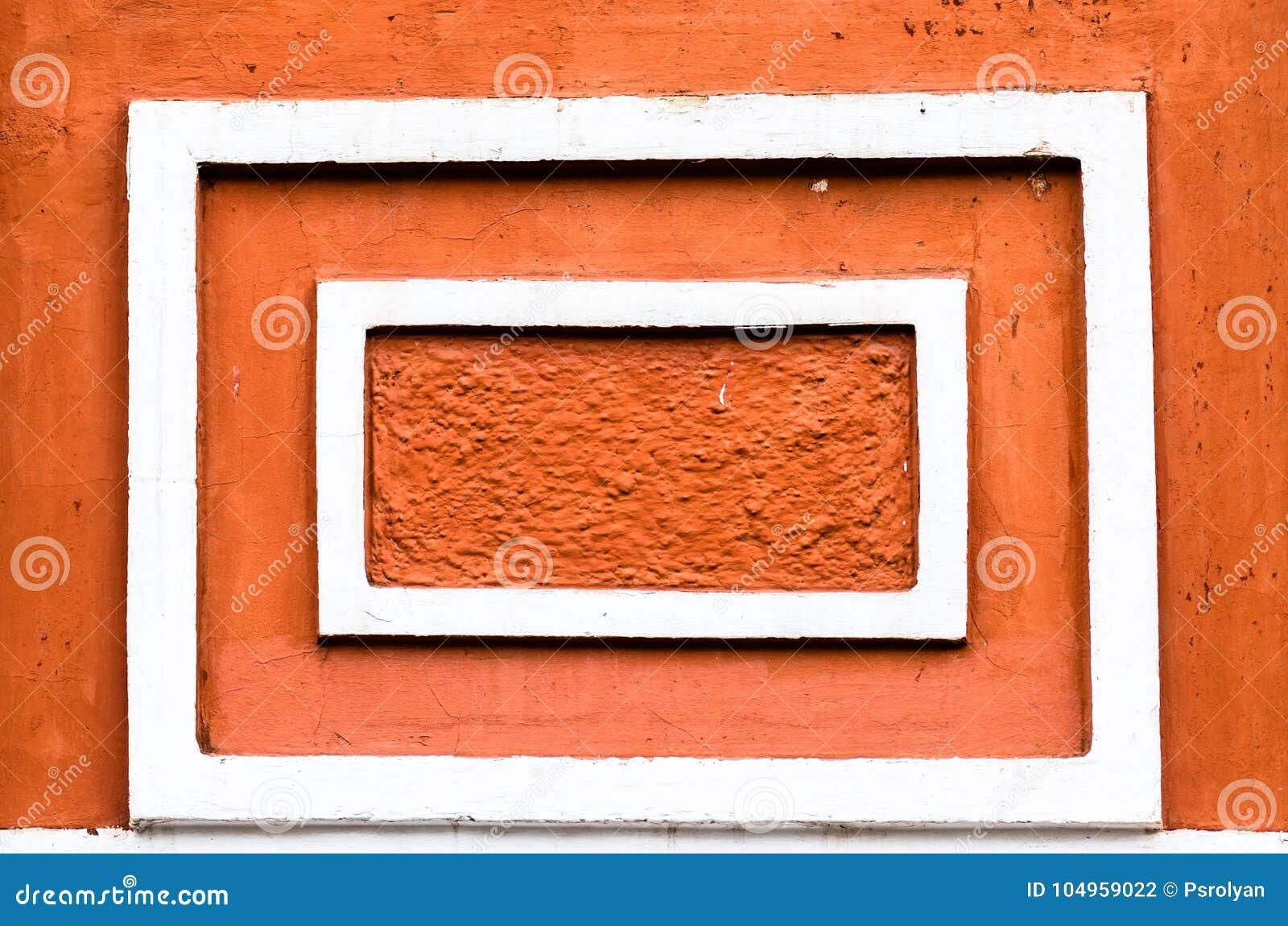 Vita tappningramar på den orange väggen