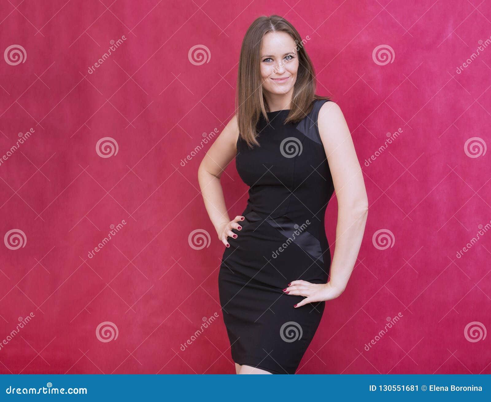 1 vita unga kvinna i åtsittande svart klänning står på röd backgroun