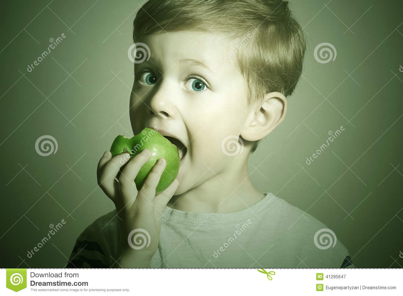 Vitamin.Child eating apple.Little Funny Boy with green apple. Health food. Fruits