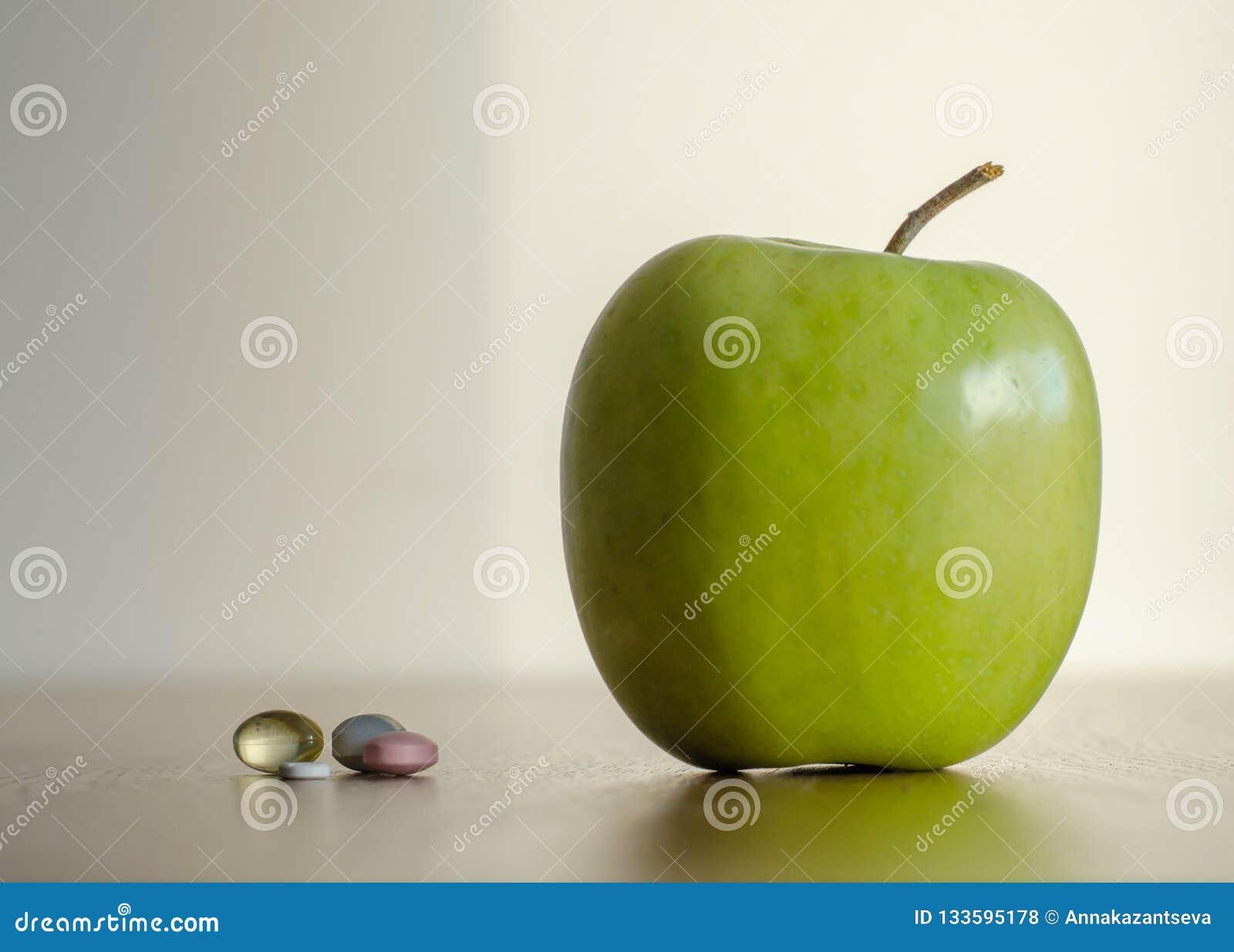 Vitamin in den Pillen gegen großen grünen Apfel Konzept des Gesundheit benef