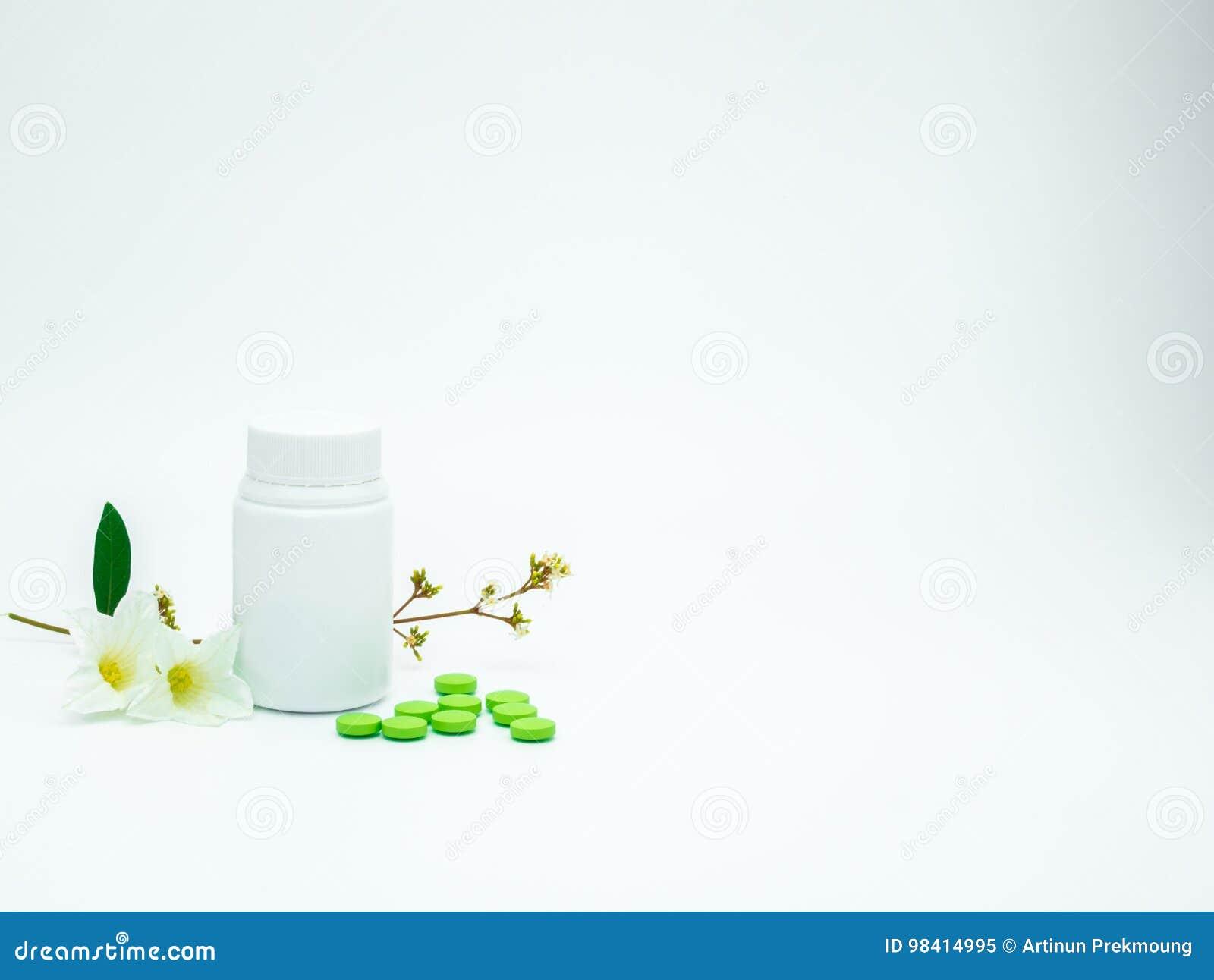 A vitamina e o suplemento marcam comprimidos com flor e ramo e anulam a garrafa plástica da etiqueta no fundo branco com espaço d