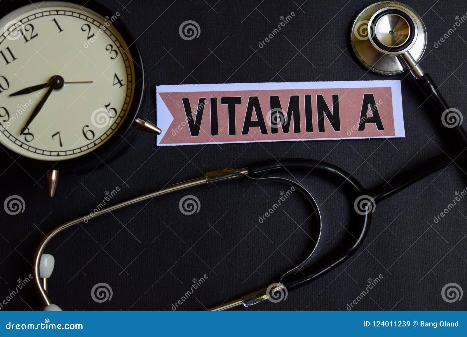 Vitamina A en el papel con la inspiración del concepto de la atención sanitaria despertador, estetoscopio negro