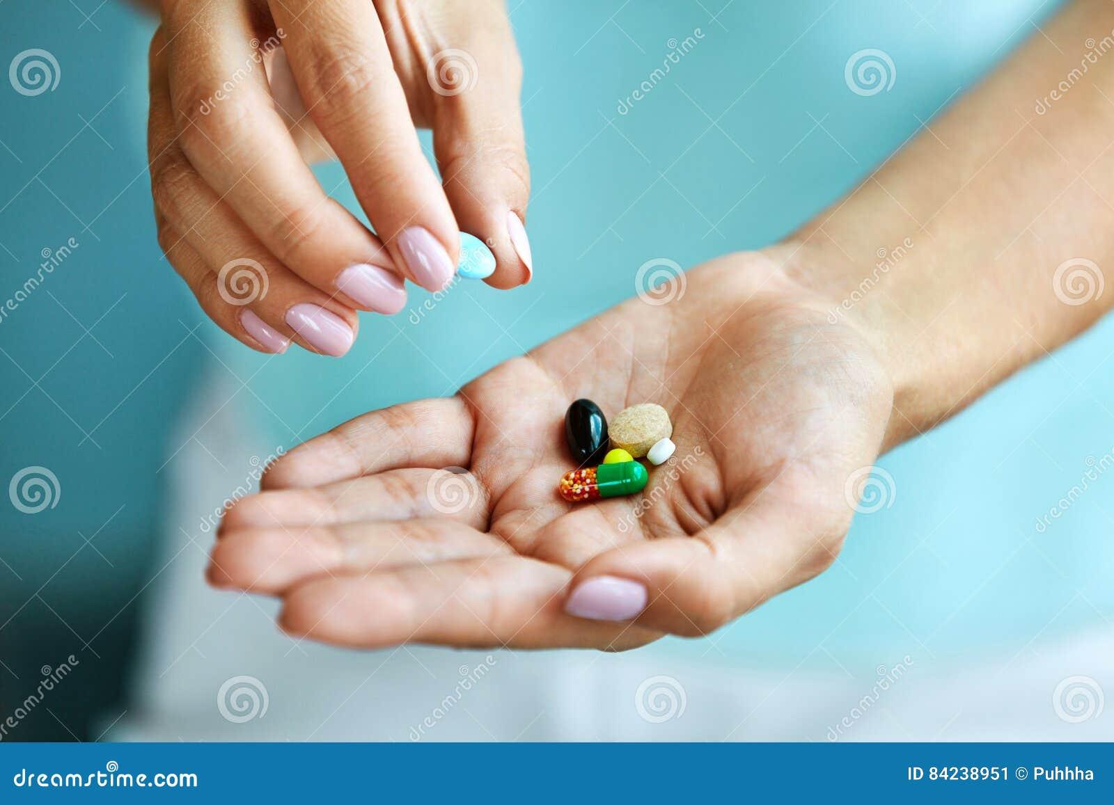 Vitaminas e suplementos Mão fêmea que guarda comprimidos coloridos