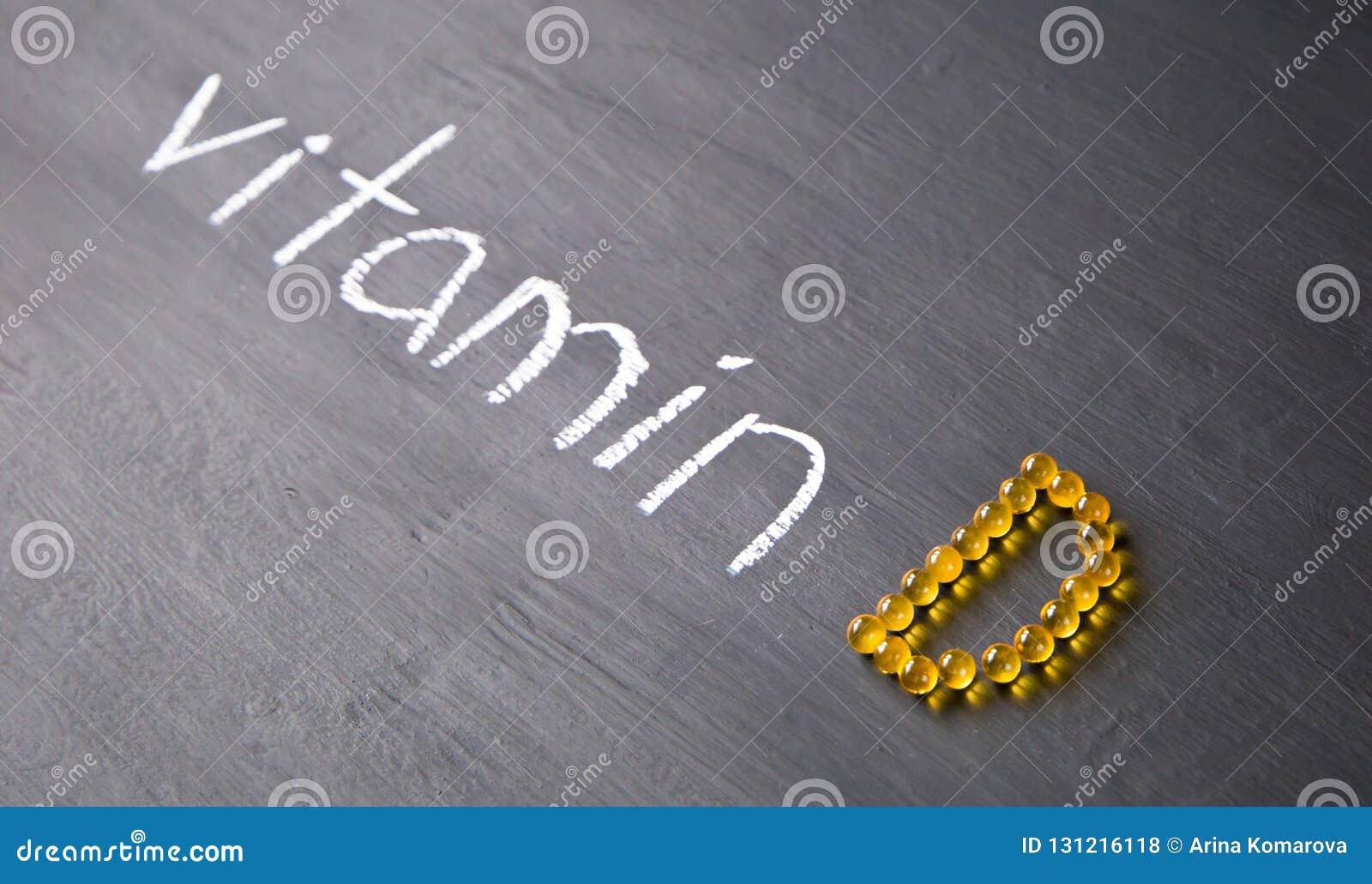 Vitamine de Word et pilules jaunes formant la forme à l alphabet de D sur le fond en bois