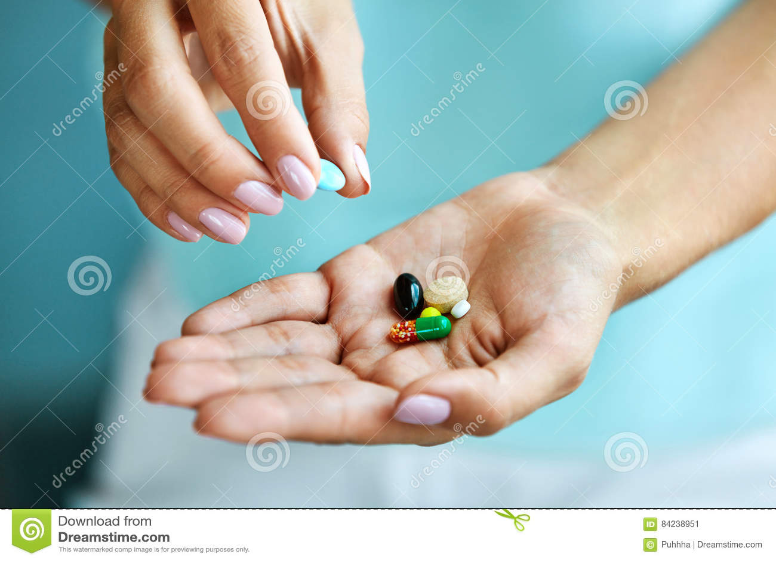 Vitamine und Ergänzungen Weibliche Hand, die bunte Pillen hält