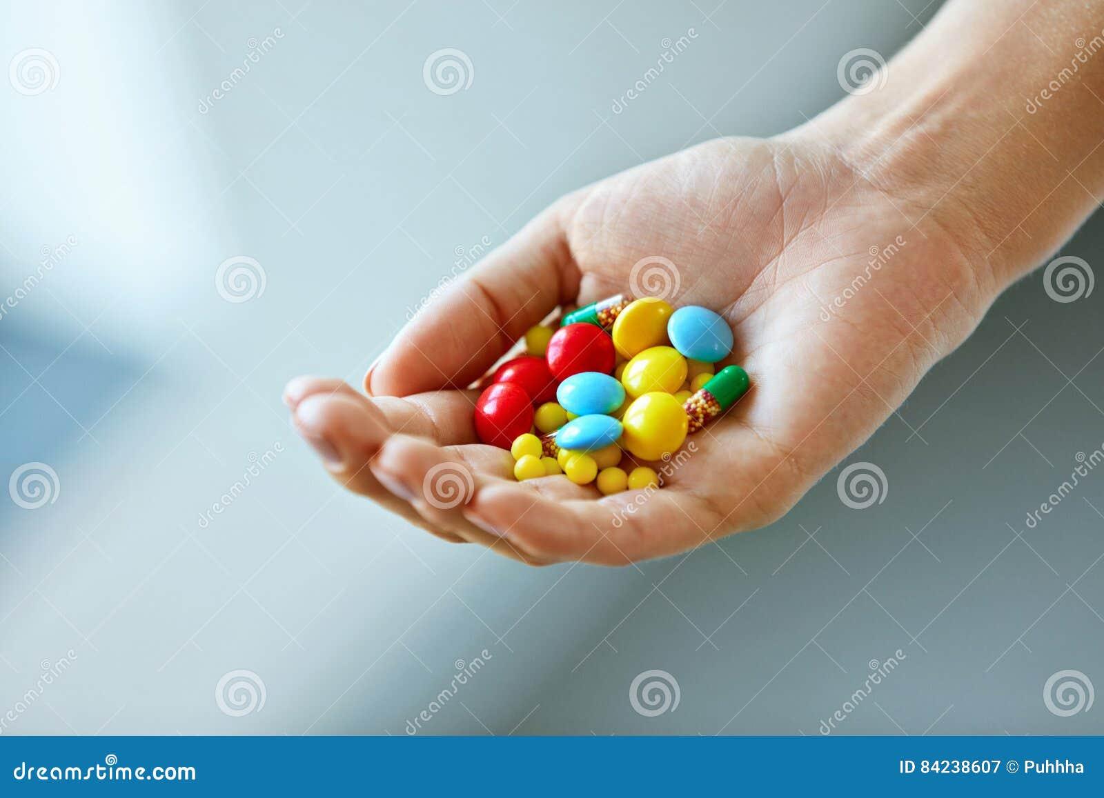 Vitamine und Ergänzungen Weibliche Hand mit bunten Pillen
