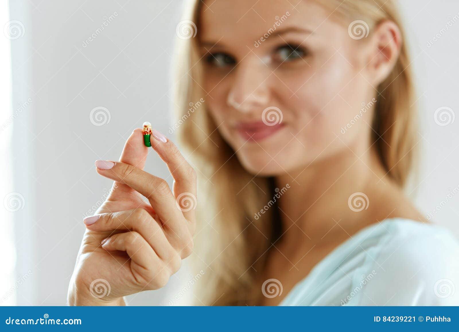 Vitamine und Lebensmittelergänzungen Schönheit mit Pille in der Hand