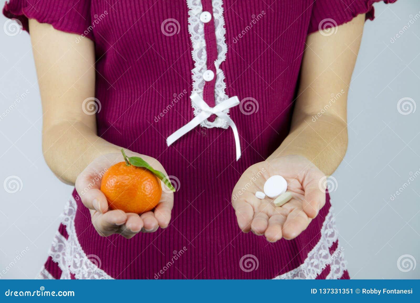 Vitamine von den Früchten oder von der Medizin? Eine junge Frau in Burgunder-Pyjamas zeigt eine Mandarine in ihrer rechten Hand u