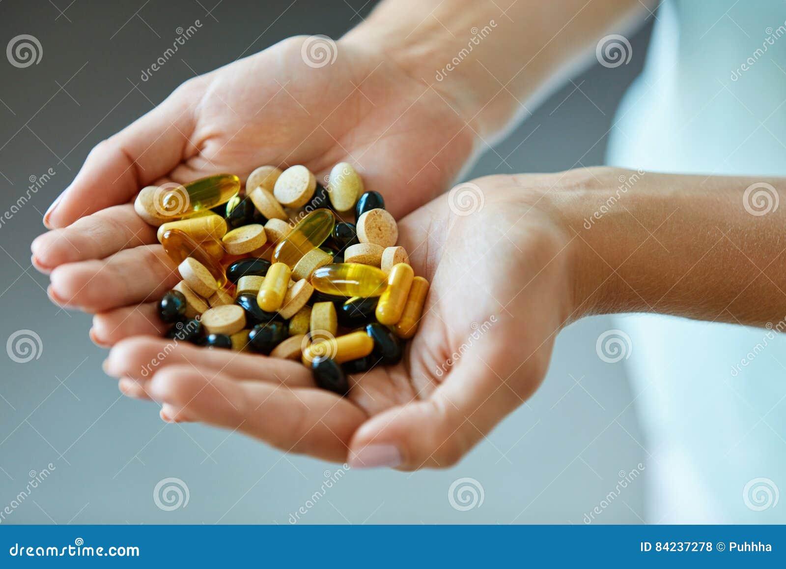 Vitaminen en supplementen Het Hoogtepunt van vrouwenhanden van Medicijnpillen