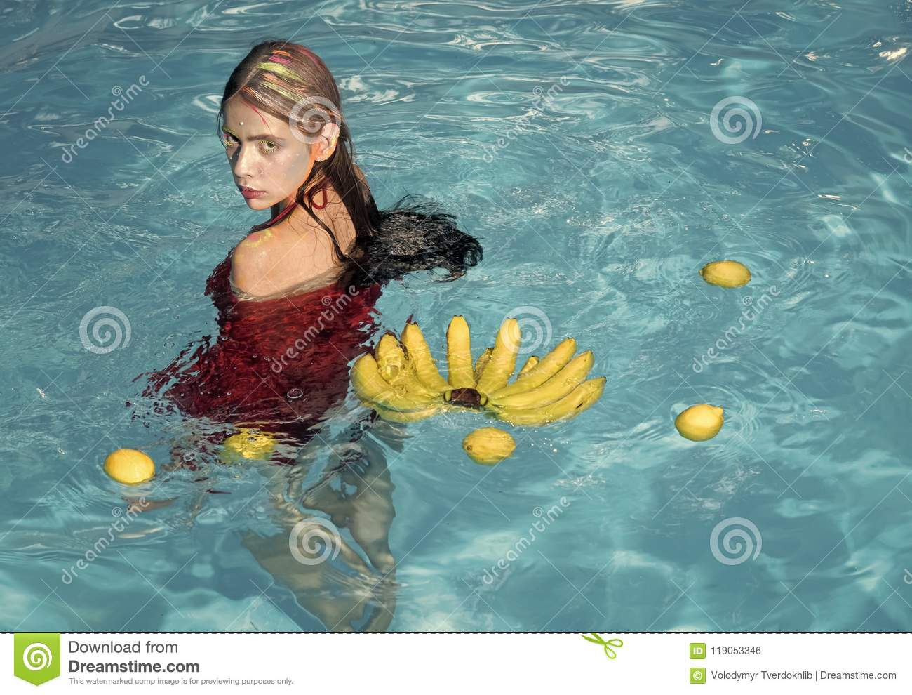 Vitamins and health. Summer vacation and travel to ocean. Vitamin in banana at girl sitting near water. Woman relax in