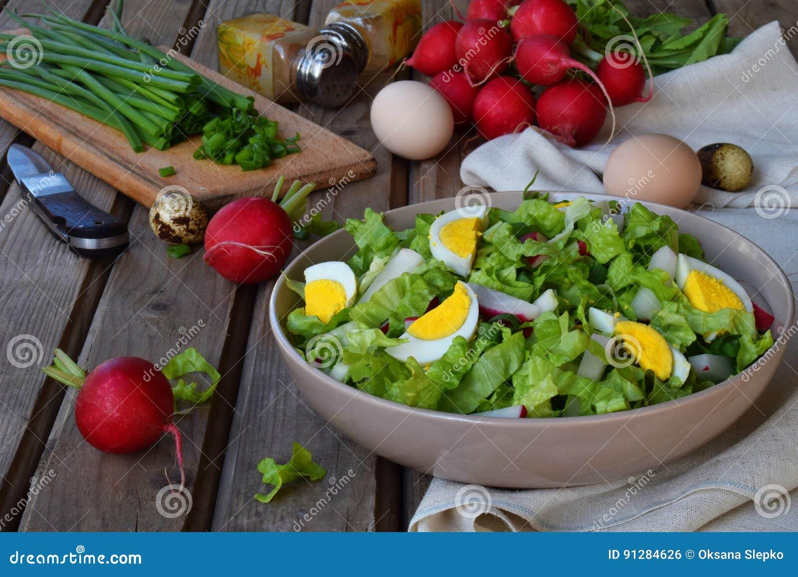 Vitaminsallad från grönsallat, rädisan, salladslökar och ägg, kryddade med grönsakolja och senap i platta på träbakgrund