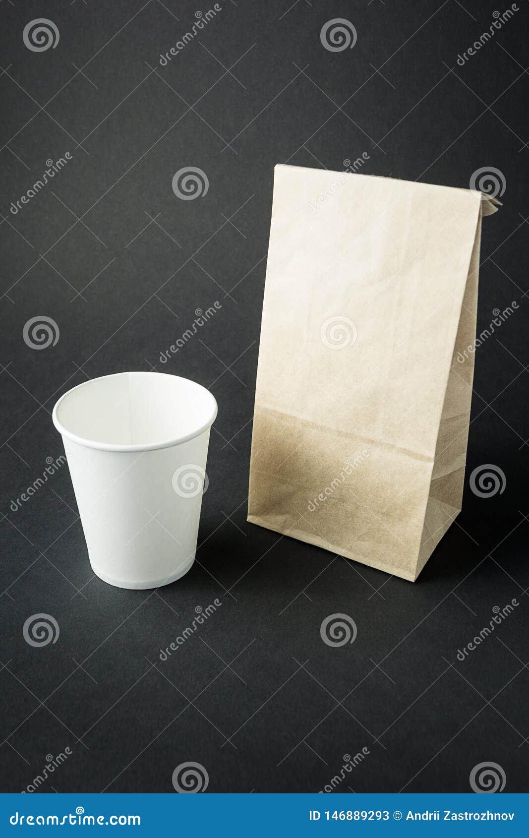 Vitbokkopp för te, kaffe eller fruktsaft som framläggas nära den mellanrum återanvända pappers- påsen som isoleras på svart bakgr