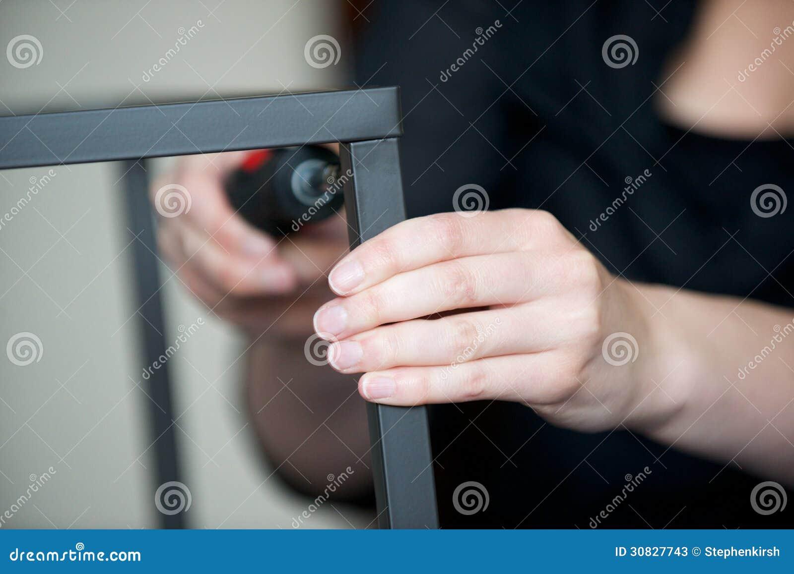 Vite delle mani insieme un pezzo di mobili metallici