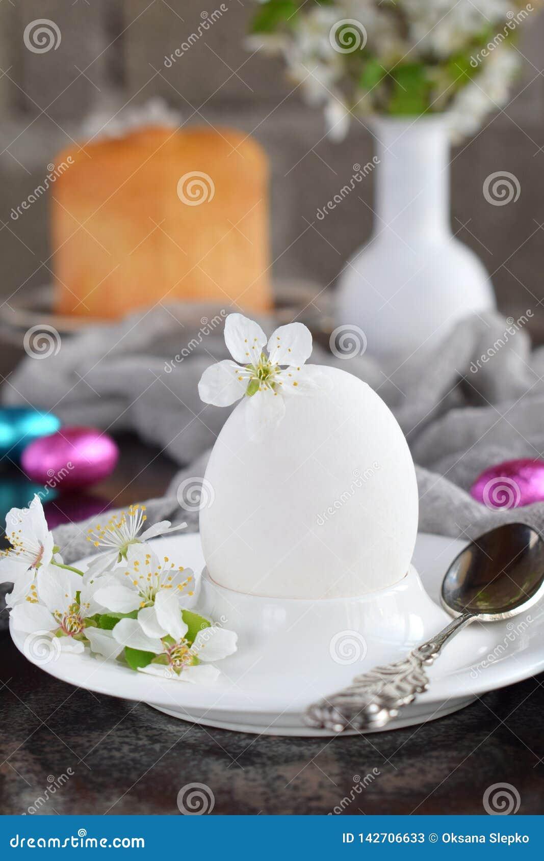 Vitt ägg och blommor på leraplattan kort lyckliga easter Feriefrukostbegrepp Festlig garnering för tabellställeinställning med