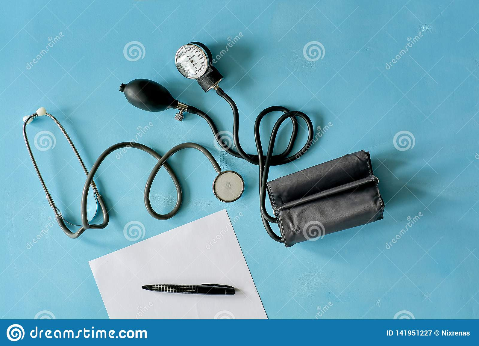 Vitt arkpapper med den svarta penn- och phonendoscopestetoskopet, sphygmomanometer på blå bakgrund