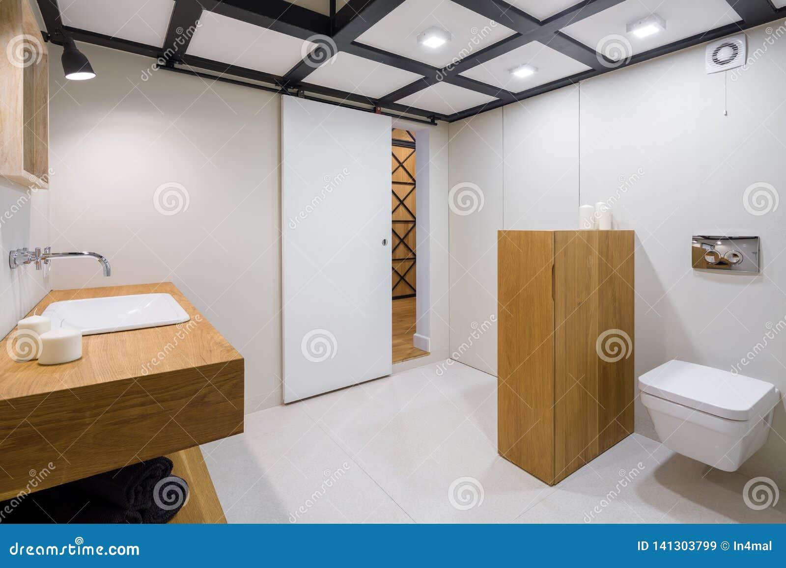 Vitt badrum med trämöblemang