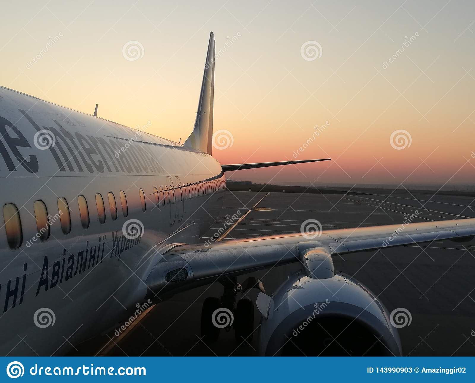 Vitt flygplan på en bakgrundssoluppgång
