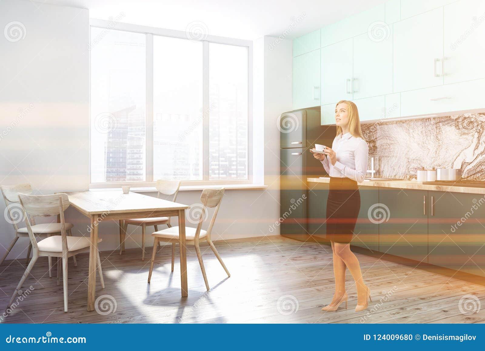 Vitt kökhörn, gröna countertops, kvinna