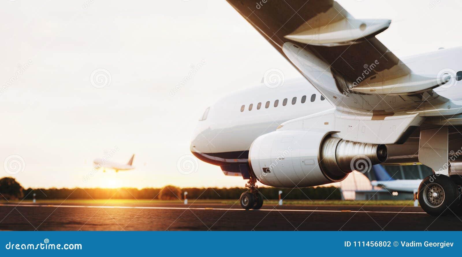 Vitt kommersiellt flygplananseende på flygplatslandningsbanan på solnedgången Passagerareflygplanet tar av