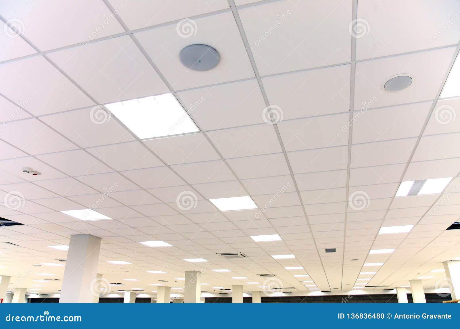 Vitt kontorstak med vita tegelplattor och belysning