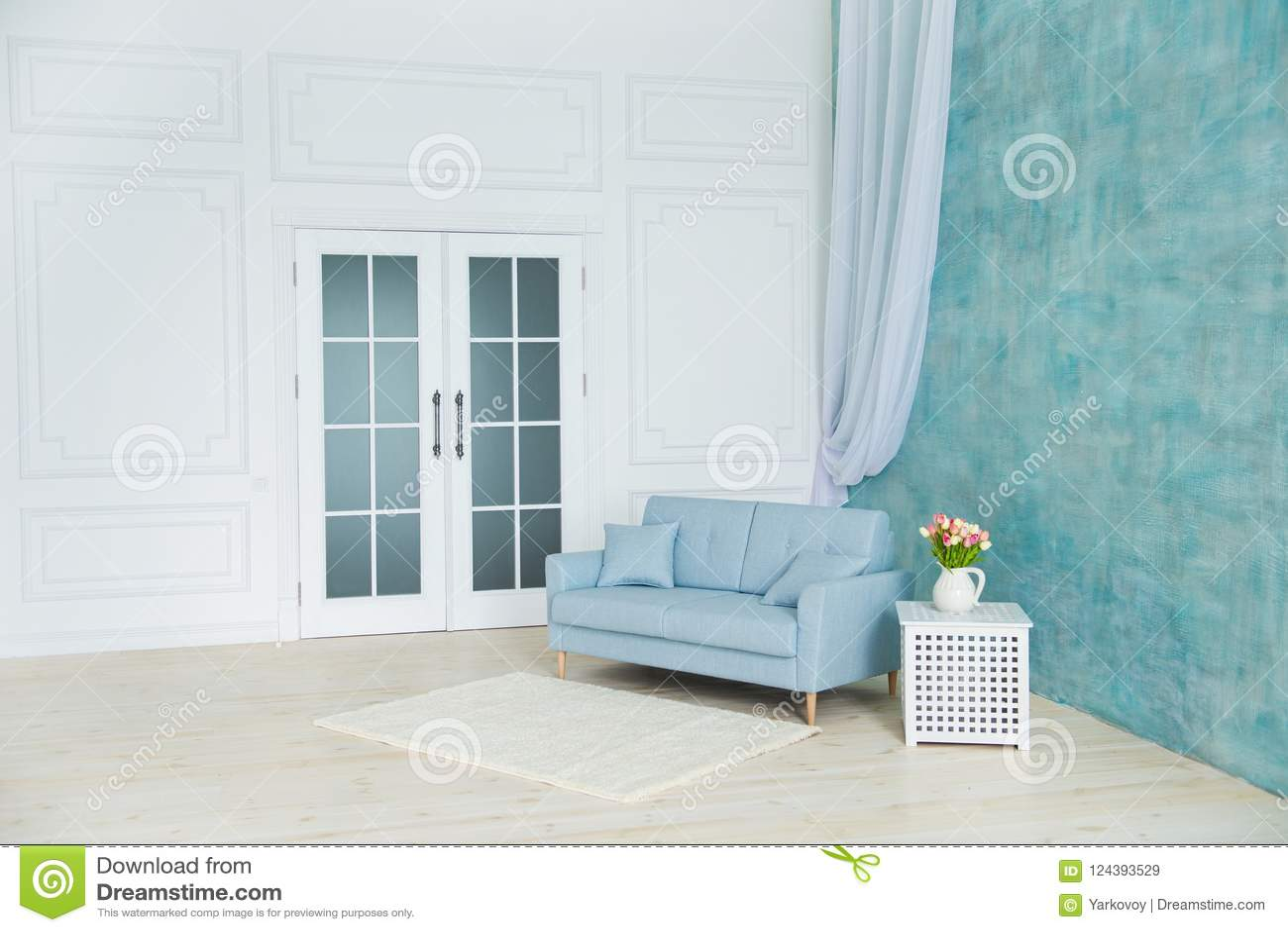 Vitt rum är en blå soffa, en sockel med blommor i en vas