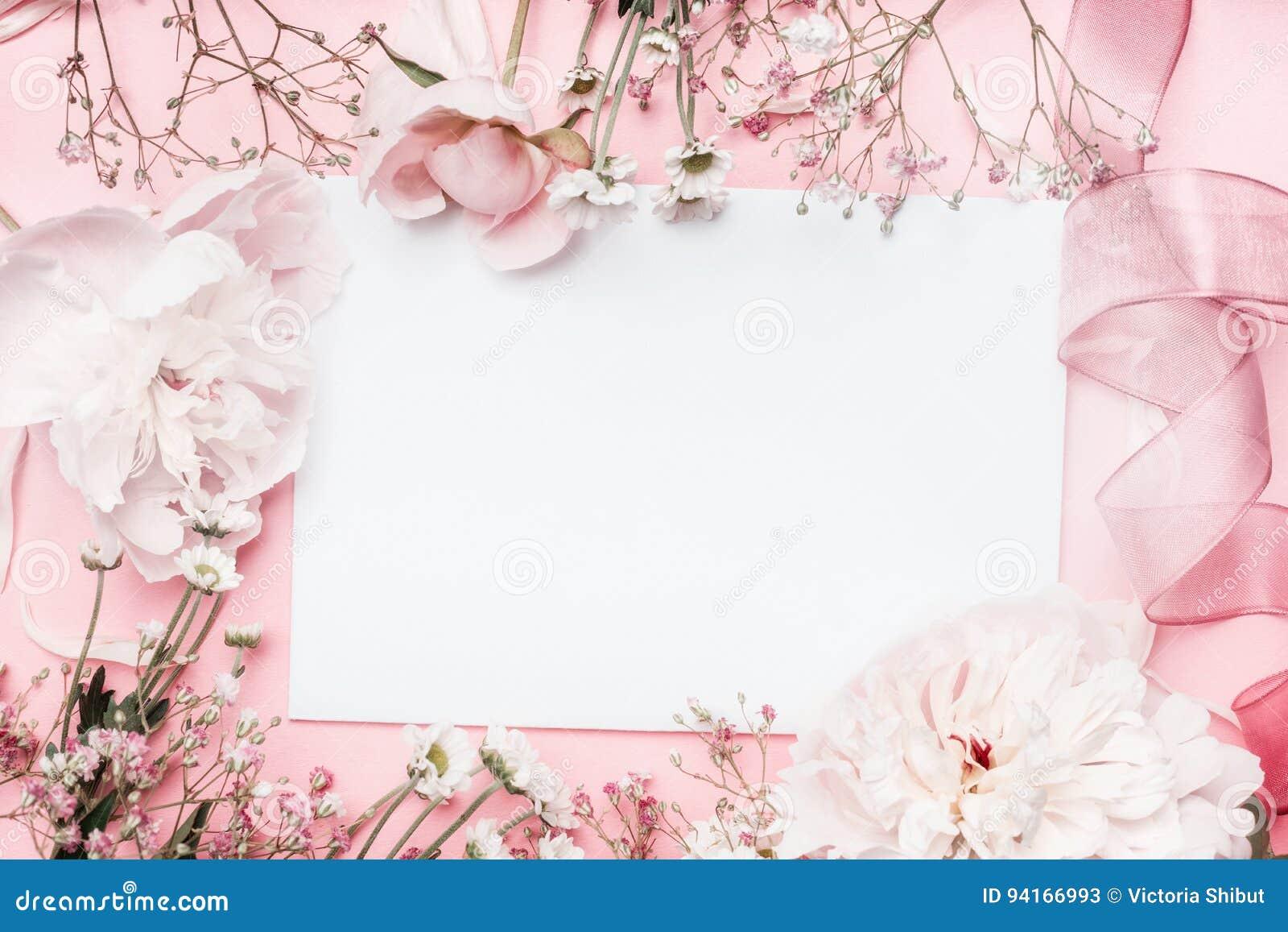 Vitt tomt kort med pastellblommor och band på rosa blek bakgrund, blom- ram Idérik hälsning, inbjudan