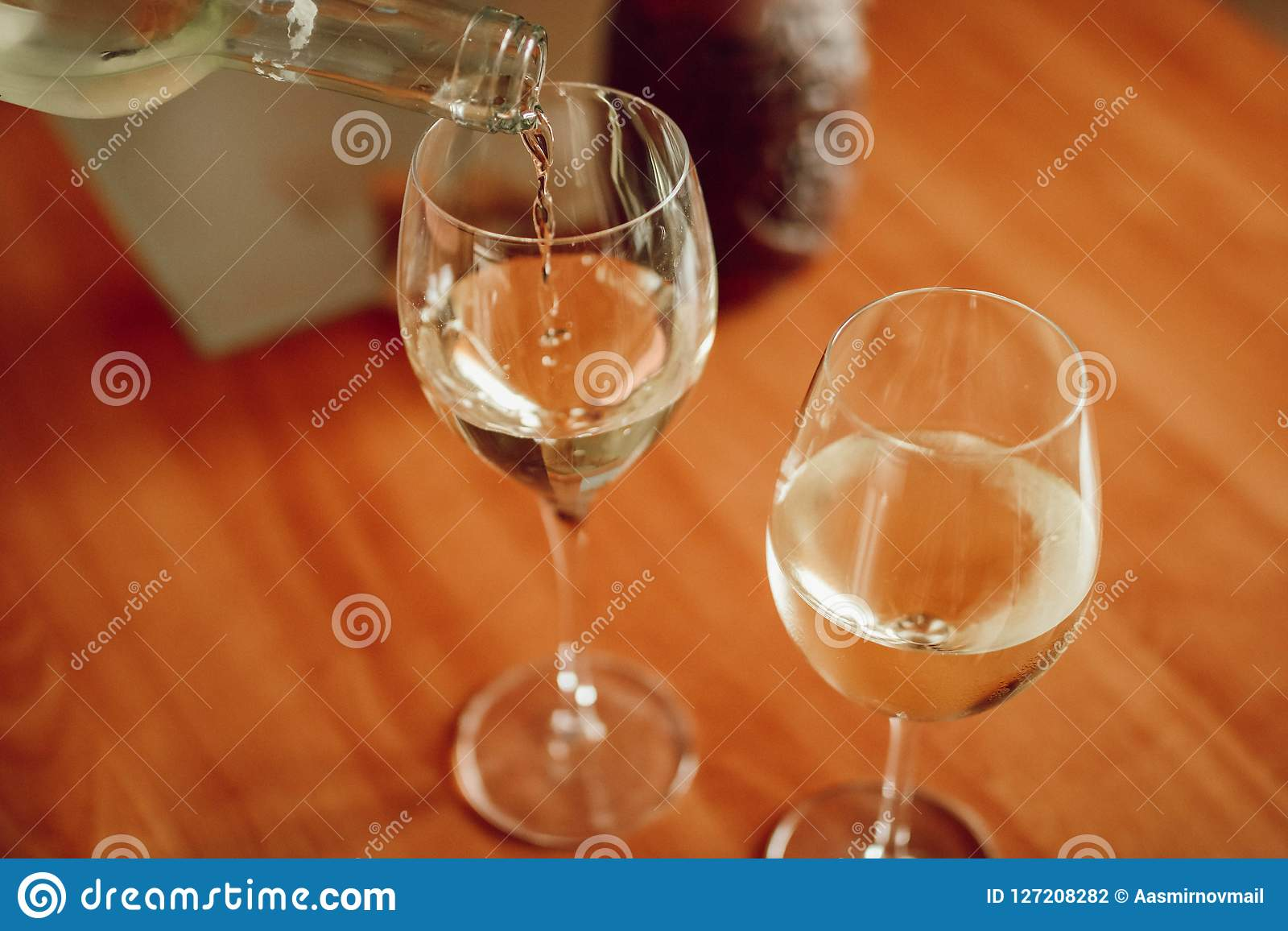 Vitt vin som häller in i exponeringsglaset ovanför sikt