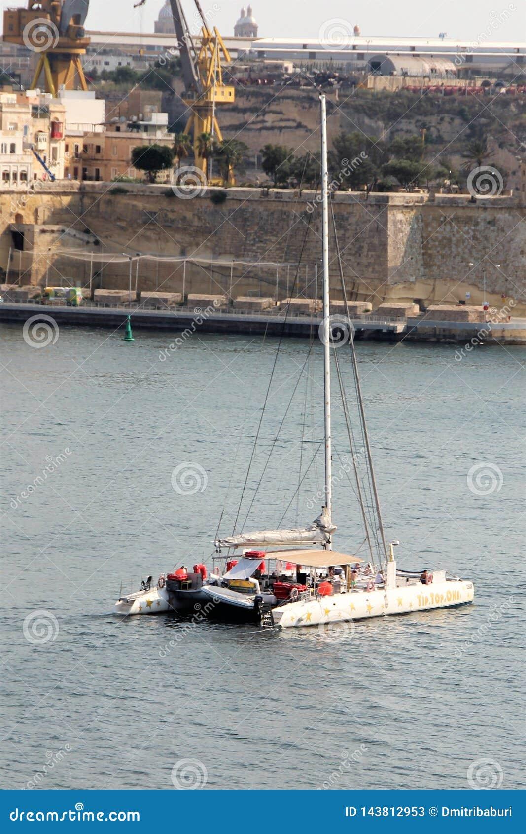Vittoriosa, Malta, Lipiec 2016 Catamaran z turystami na tle forteczne ściany antyczny miasto