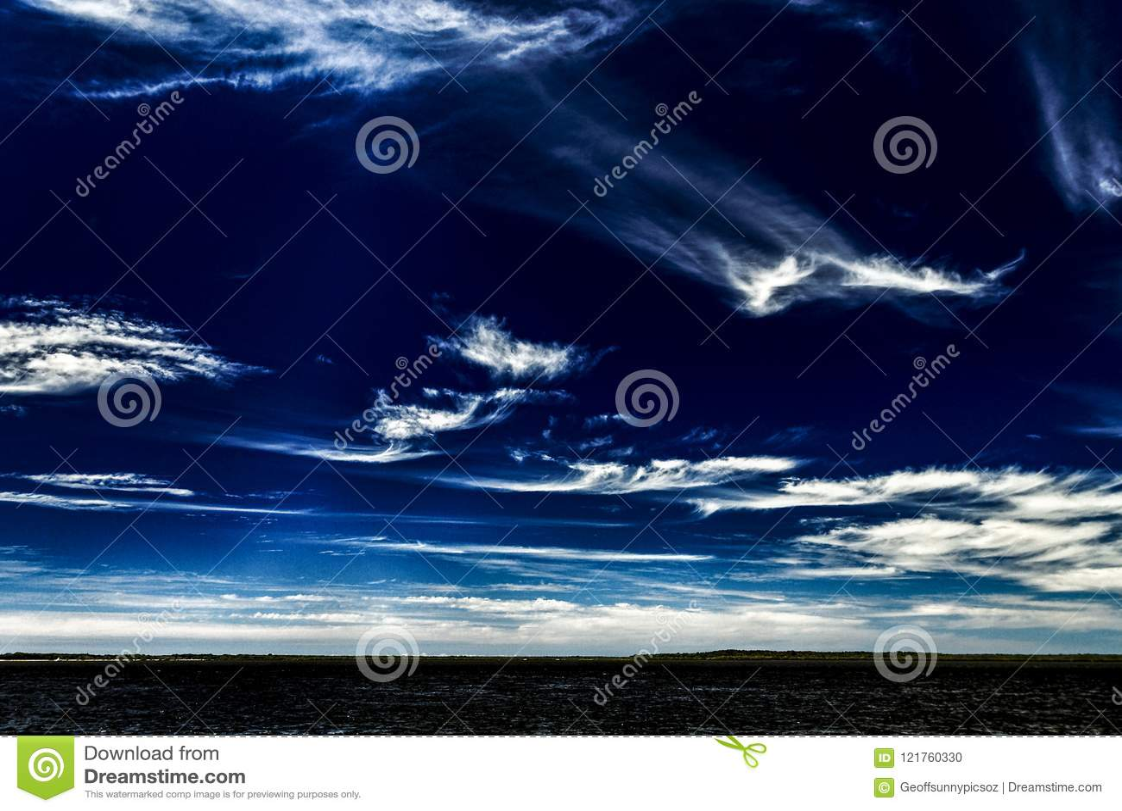 Vivid white Cirrus cloud in dark blue sky.