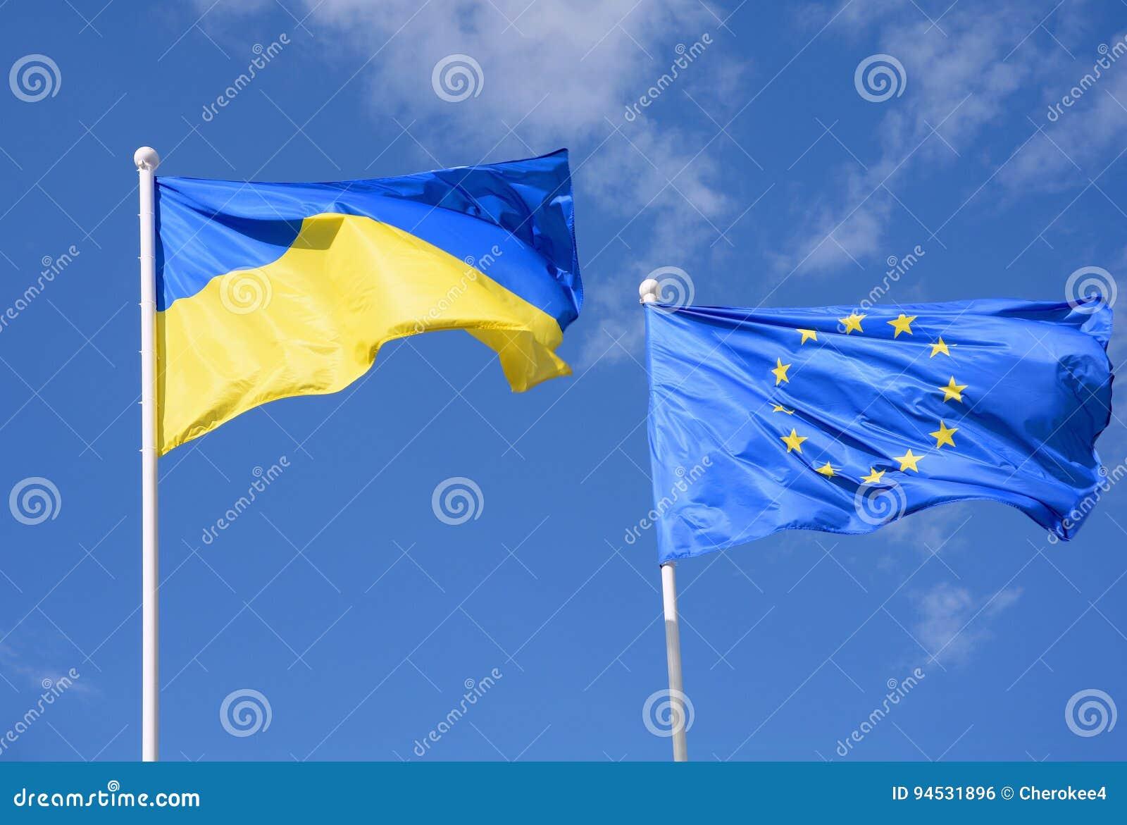 Vlaggen van de Europese Unie van de Oekraïne en de EU tegen de blauwe hemel