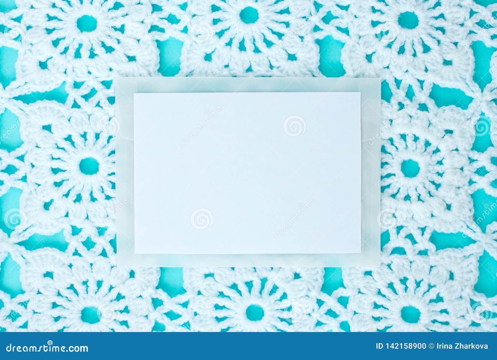 Vlak, leg, een blad van document voor tekst op een blauwe achtergrond met gehaakt wit uitstekend kant, de winterthema, vierkant o